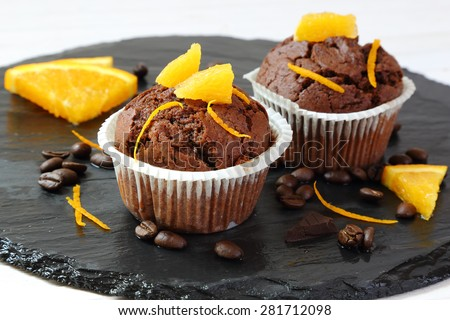 Chocolate muffins with oranges on a black tray, selective focus - stock photo