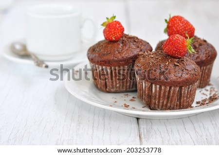 Chocolate muffins with strawberries, selective focus