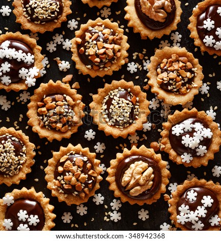 Chocolate nut small tarts on a dark background. A delicious Christmas dessert - stock photo