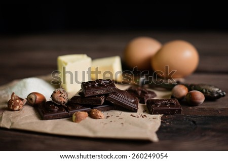 Chocolate, nuts, butter and eggs. Ingredients for Brownie and chocolate cake on the table, dark background  - stock photo