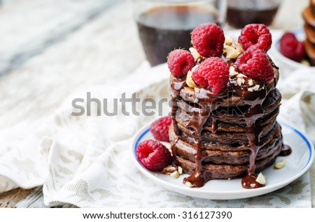 chocolate pancake with bananas, raspberies, nuts and chocolate sauce. the toning. selective focus - stock photo