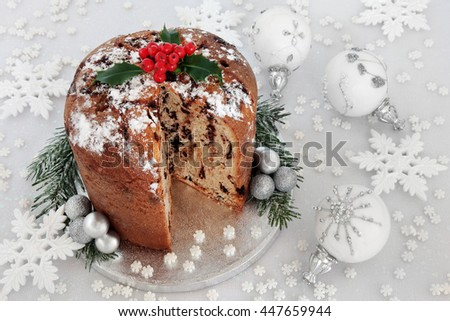 Chocolate panettone christmas cake with holly berries, white and silver snowflake and bauble decorations.