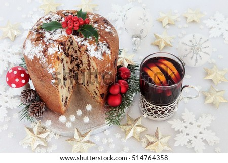 Chocolate panettone christmas cake with mulled wine and star,snowflake and round shaped bauble decorations.