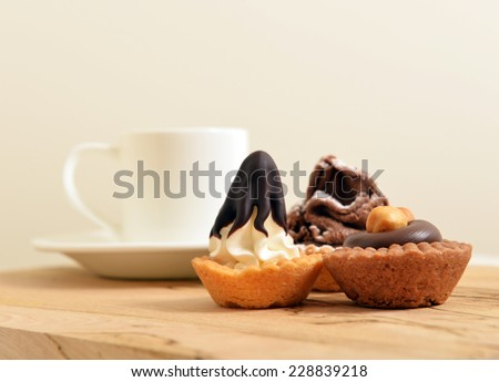 chocolate pastry with a White coffee cup on a wooden board shallow dof - stock photo