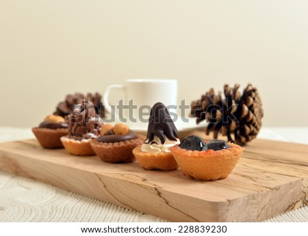 chocolate pastry with coffee cup and pine cones on a wooden board shallow dof - stock photo
