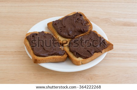 Chocolate peanut butter on hard toast atop a white plate and table top illuminated with natural light. - stock photo