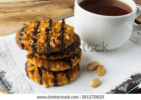 Chocolate Peanut cookies and a cup of tea on a metal serving tray with white lace napkin. Breakfast biscuits and tea. Homemade chocolate peanut cookies. Cookies. Pastry. Biscuits. Homemade cookies - stock photo
