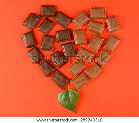 Chocolate pieces arranged in heart shape on red background - stock photo