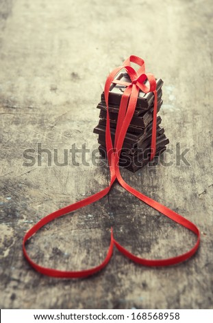 Chocolate pieces in decorative ribbon on wooden table - stock photo
