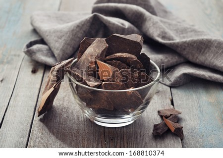 Chocolate pieces in glass bowl  on wooden background - stock photo