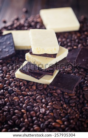 Chocolate pieces on coffee beans  on dark wooden background. Selective focus. Rustic style. - stock photo