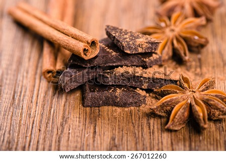 chocolate pieces, star anise and cinnamon sticks close up - stock photo