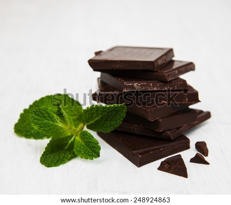 Chocolate pieces with a leaf of mint on white wooden background