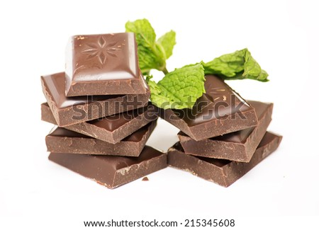 Chocolate pieces with mint leaves on a white background.