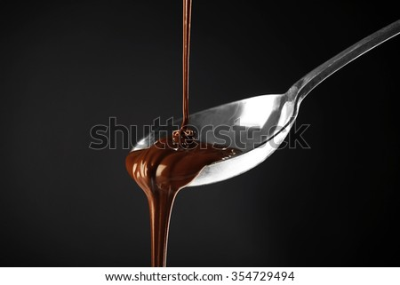 Chocolate poured on a spoon on dark background - stock photo