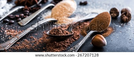 Chocolate powder cocoa and coffee spoons on the table black - stock photo