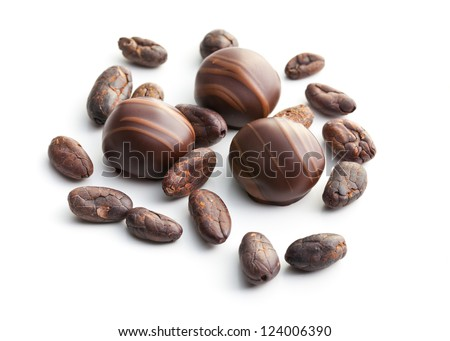 chocolate pralines and cocoa beans on white background