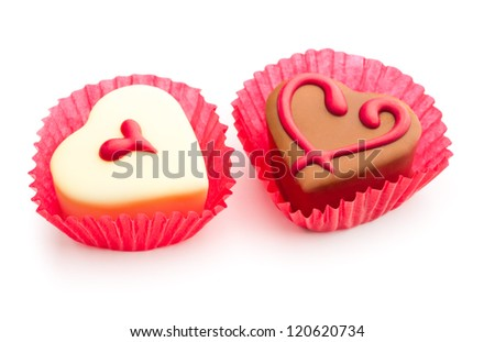 Chocolate pralines decorated with heart shapes on white backgr?und - stock photo