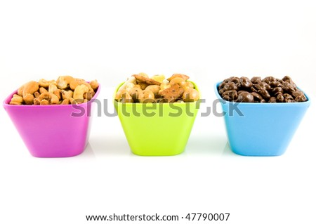 Chocolate raisins, cashew nuts and mixed nuts in colored bowls isolated on white background - stock photo