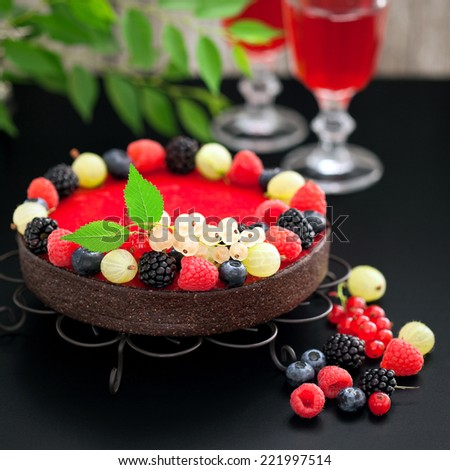 Chocolate raspberry tart with fresh berries, selective focus - stock photo