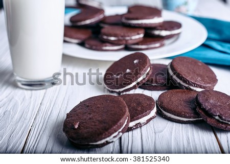 Chocolate sandwich cookies with cream filling on wood background. Glass of milk at background - stock photo