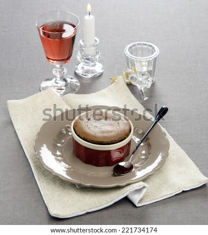 chocolate souffle on a festive table with a wine glass in the background with candles - stock photo