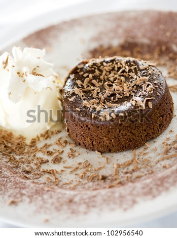 Chocolate souffle on plate with whipped cream and chocolate flakes
