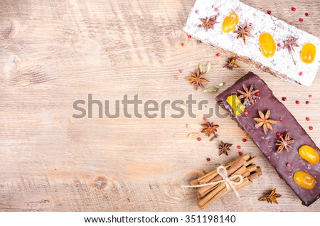 Chocolate spices cake with star anise and dried fruits, cinnamon, cloves, cardamom, handmade milk chocolate with nuts on wooden background. Christmas gift. - stock photo