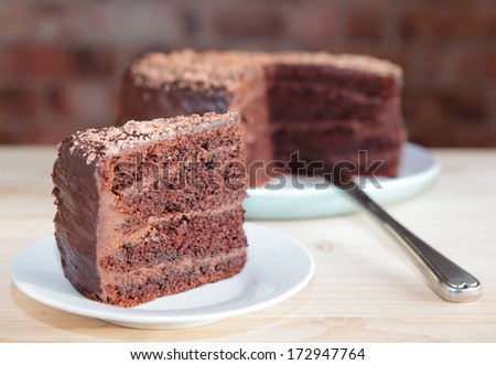 Chocolate sponge cake with chocolate buttercream frosting and ganache, cut out, selective focus - stock photo