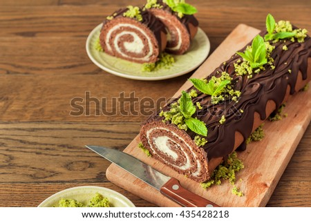 Chocolate sponge roll with with cream and spinach biscuit on wooden background - stock photo