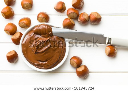 chocolate spread in bowl on wooden table - stock photo