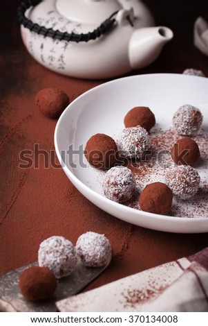 Chocolate sweets with cocoa and coconut chips on a white plate, selective focus - stock photo