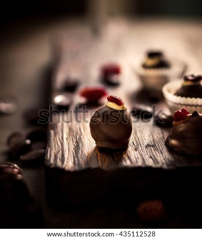 Chocolate sweets with dried berries and chocolate beans on dark chopping board. Dark stone background. Selective focus. Toned image. - stock photo
