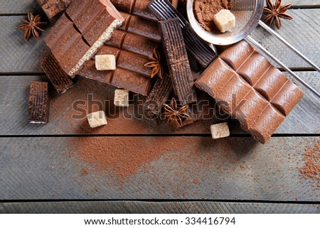 Chocolate sweets with powder on wooden background - stock photo