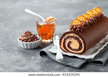 Chocolate swiss roll cake with candied kumquats, selective focus - stock photo