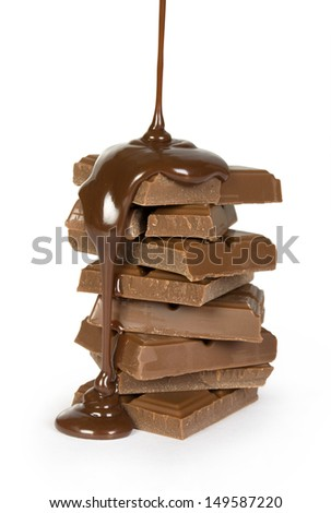 Chocolate syrup being poured over stack of bars on white background - stock photo