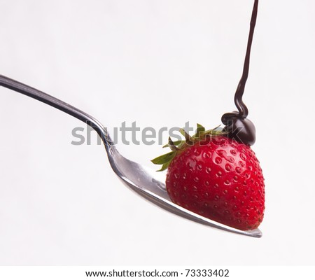 Chocolate Syrup hits the berry Fruit Raw Food Strawberry sitting on Silver Spoon