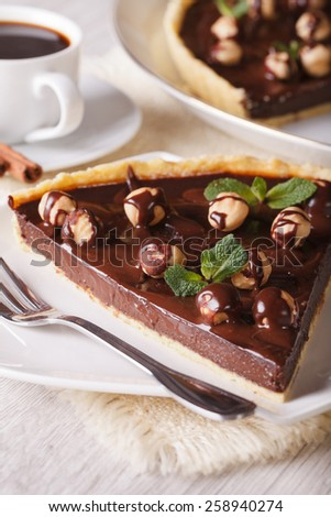 Chocolate tart with hazelnut and coffee on the table close-up. Vertical