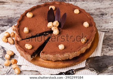 chocolate tart with hazelnuts on a wooden plate - stock photo