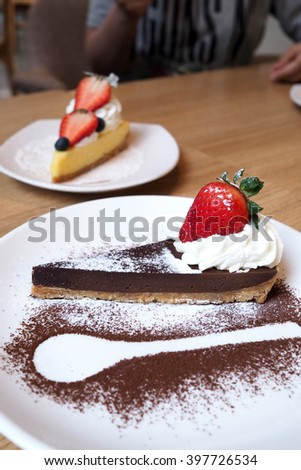 chocolate tart with strawberry and whipped cream decorated with spoon outline   - stock photo