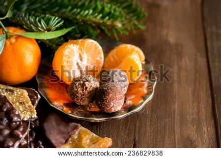 Chocolate, truffles and tangerines  on a wooden table - stock photo
