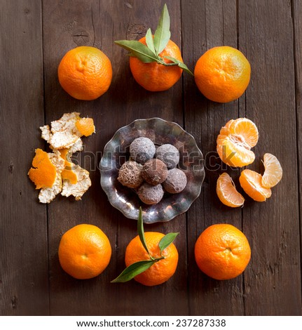 Chocolate truffles and tangerins on a wooden table - stock photo