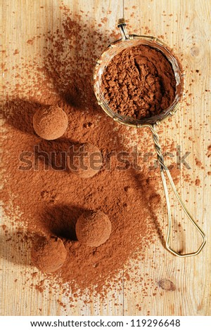 chocolate truffles cocoa powder dusted and sieve, shallow dof - stock photo