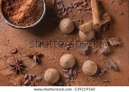 Chocolate truffles with bowl of cocoa, black chocolate flakes, cinnamon sticks, anise and cocoa powder as background. Top view with space for text