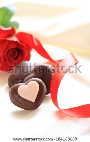 Chocolate valentine hearts and a red rose on a table. - stock photo