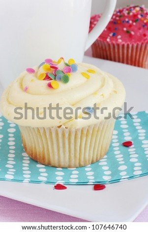 Chocolate, vanilla and strawberry cupcakes with multi-colored sprinkles
