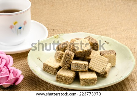 Chocolate wafer in dish with a cup of tea on brown sack background - stock photo