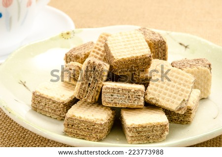 Chocolate wafer in dish with a cup of tea on brown sack background