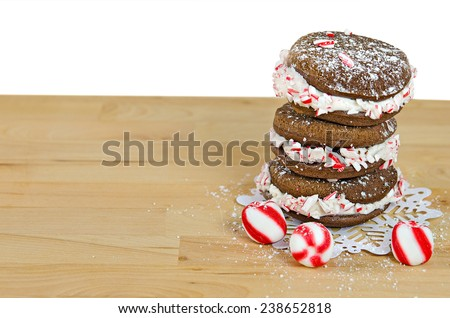 chocolate whoopie pie with crushed candy cane on snow flake lace doily - stock photo