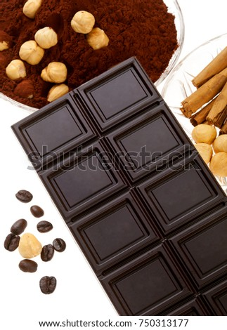 Chocolate with coffee beans, cocoa powder, cinnamon and dried orange on white background.